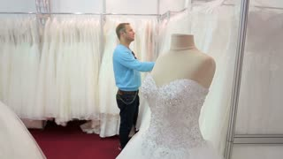 The young man puzzled looks at the dresses in the Bridal salon.