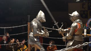Two medieval knight fighting in the arena with two-handed swords. Slow motion. Great Knights tournament