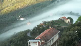 Early foggy morning in the Alpine town. Fog from the mountains makes its way along the medieval streets. Perinaldo, Liguria, Italy.