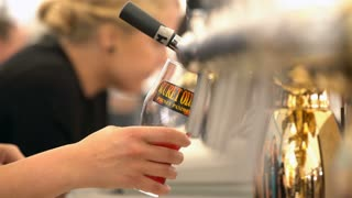 HELSINKI, FINLAND - JULY 29, 2017: Barmen pour beer from beer taps. Beer Fair in the Railway Square in Helsinki