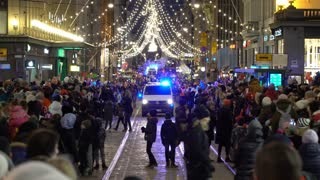 HELSINKI, FINLAND - NOVEMBER 26, 2017: Police car with flashing lights slowly moving among the festive crowd