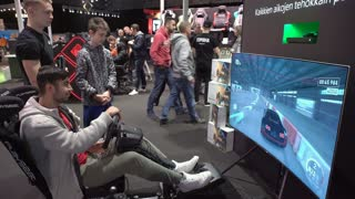 HELSINKI, FINLAND - NOVEMBER 3, 2017: Young men playing new games from XBOX ONE X car race with the wheel. Newest gadgets on GAME EXPO in the exhibition center Messukeskus
