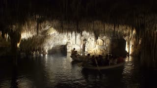 MAJORCA, SPAIN - 06 SEPTEMBER 2017: Tourists float on a boat on the underground lake in the famous stalactite caves of Dragon (Cuevas del Drach