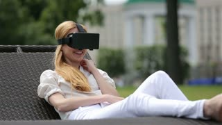 Virtual reality mask. Girl with pleasure uses head-mounted display in a city park.