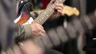 Visitors music salon testing new electric guitar.