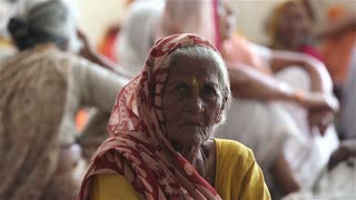 VRINDAVAN, INDIA - JULY 11, 2015: Old Indian woman sitting on the floor in the Ashram among other widows.