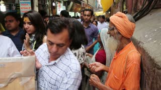 VRINDAVAN, INDIA - JULY 14, 2015: Buddhist monk beggar asks for alms from passers-by on the street in India.