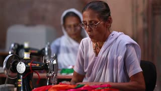 VRINDAVAN, INDIA - JULY 15, 2015: Elderly Indian women in traditional sari sew clothes using mechanical sewing machines in the Ashram.