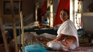 VRINDAVAN, INDIA - JUNE 14, 2015: Elderly Indian smiling woman sitting on her bed in dormitory room in the Ashram.