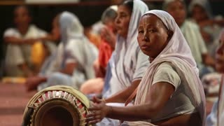 VRINDAVAN, INDIA - JUNE 15, 2015: Indian woman in a sari plays a traditional drum during a religious rite Krishna.
