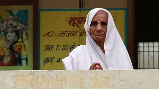 VRINDAVAN, INDIA - JUNE 15, 2015 : Old Indian woman in a white Sari of the widow in the courtyard of the Ashram.