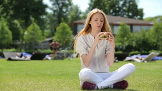 Young slim woman with an appetite for eating a hamburger in a city park.