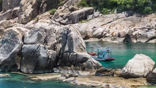 Fisher boat moving on waves at anchor between huge stone blocks in Tanote Bay, Koh Tao Island, Thailand.
