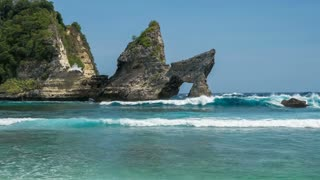 Huge wave hit the Rock stick out of the ocean at Atuh beach,. Foam is splashing over the Rock. Nusa Penida, Indonesia