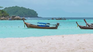 Long tail boats swinging in blue water with white sand beach in front waiting for tourist, Koh Lipe island, Thailand