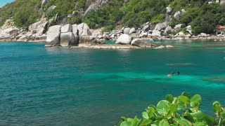 Tanote Bay on sunny day. Rippled ocean water over beautiffull Coral Reef. Divers practice in the blue bay. Koh Tao, Thailand