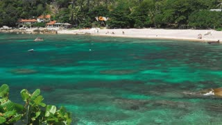 Tanote Bay on sunny day. Rippled ocean water over beautiffull Coral Reef. Tourist chill on sandy beach. Koh Tao, Thailand