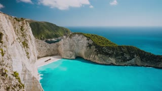 Timelapse of the world famous Navagio beach, Zakynthos, Greece. Turquoise sea water rolled to white sand beach with Shipwreck. Clouds moving in sky. Fist tourist boat arrived the bay