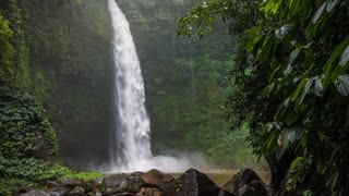 Tropical waterfall in lush green jungle. Falling water hitting water surface. Green leaves moved by the wind breeze