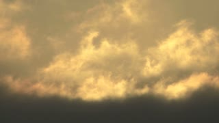 Close shot of quickly moving clouds at sunset