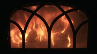 Flames behind glass door of a wood burning stove