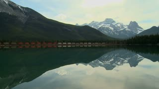 Freight train and mountains reflected in lake