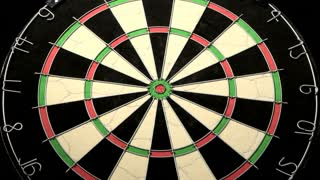 Medium wide shot with three darts, last one hits the target