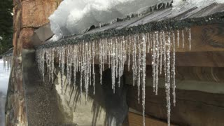 Mountain cabin with a row of melting icicles dripping off the roof