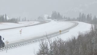 Semi trailer trucks and other traffic on a snowy winter highway