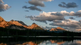Sun rises and lights distant mountain range with cloud and lake movement, Canadian Rockies, Alberta, Canada