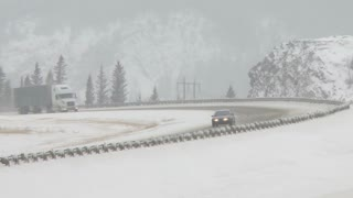 Telephoto shot of a semi trailer truck on a snowy winter highway