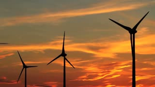 Three wind turbines with the brilliant sky of a setting sun, Alberta, Canada