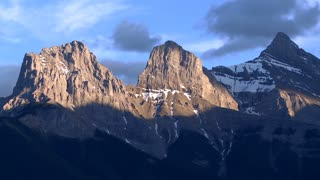 Time lapse of setting sunlight on The Three Sisters mountain group, Canadian Rockies, Alberta