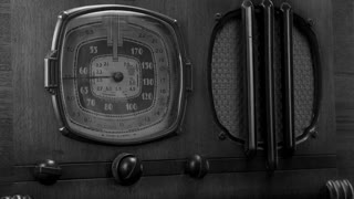 Vintage radio tuned by a woman, black and white