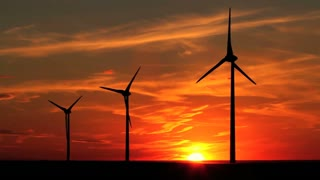 Wind turbines with the brilliant sky of a setting sun, Alberta, Canada