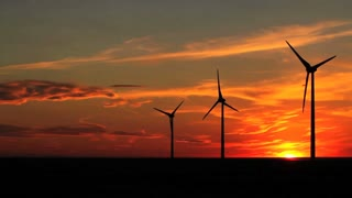 Wind turbines with the brilliant sky of a setting sun, Alberta, Canada