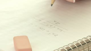 Woman's fingers erasing math equation
