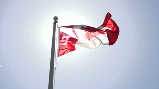 A sunlit Canadian flag flies in slow motion.