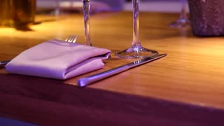 Empty wine glasses on a wooden table at a restaurant - Tilt up