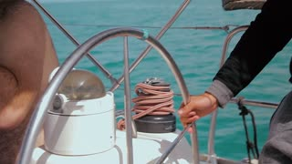 Man controls the steering wheel of a sailing boat. Closeup on his hand.