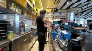 Jerusalem, Israel - May 11, 2017: Timelapse of busy staff members serving customers in coffee shop. People sitting near tables, eating and drinking.
