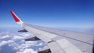 Airplane Wing out of Illuminator Window and Blue Sky