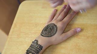 Artist Applying Henna Tattoo on Women Hand. Mehndi