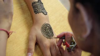 Artist Drawing Henna Tattoo on Woman Hand in India