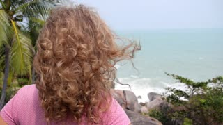 Back View of Young Woman with Curly Hair Enjoying Sea View