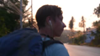 Backpacker Man Hitchhiking on Road at Sunset in Travel