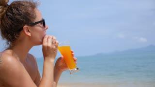 Beach Woman Drinking Cold Juice Enjoying the Sea.