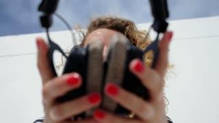 Beautiful Female with Headphones Enjoying Music Outdoors.