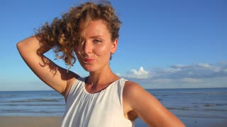 Beautiful Girl with Curly Hair Flirting at Beach. Emotions.