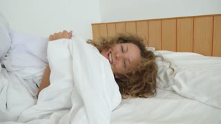 Beautiful Girl with Curly Hair Lying in Bedroom in White Bed